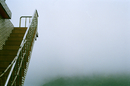 Stairs in the foreground on left and white foggy abstract landscape. Taiwan. 2010